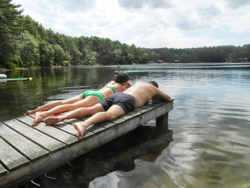 swimmers relax on dock in Myles Standish State Forest